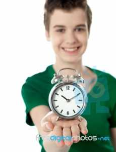 smiling-boy-showing-alarm-clock-10094033